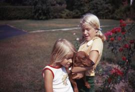 Two unknown young girls with a dog