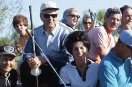 Group of unknown people, likely sitting on hay bales, holding golf clubs