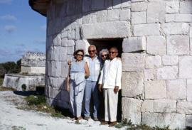Dr. Irving and Phyliss Snider and an unknown man and woman posing in front of a stone building