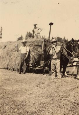 Farmers with a horse and cart full of hay