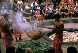 Luau with two men in traditional dress carrying a roasting pig