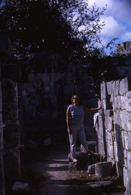 Phyliss Snider looking up at the sky while posing next to a stone wall