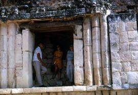 Unknown man and two unknown woman resting in the shade of the doorway of a Mayan ruin