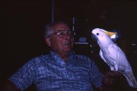 Dr. Irving Snider with a white parrot on his hand