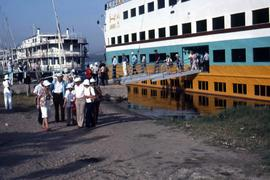 "Groups of unidentified people disembarking from a ship with the word ""Anni"" on it"
