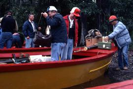 Group of men taking their bags and supplies out of small red and yellow fishing boats