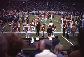 Football players on a football field with people lined up holding flags on the right and left of ...
