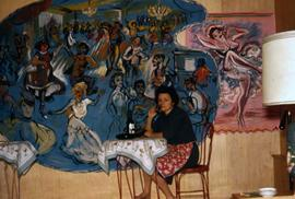 Phyliss Snider sitting at a cafe table with with two paintings behind her