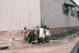 Group of children gathered around a water fountain