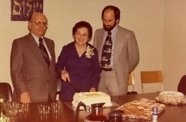Two men and one woman at table cutting a cake