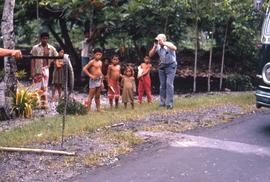Children standing next to a man taking a picture of a snake held up on a stick