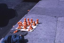 Oranges piled on a piece of newspaper on a sidewalk