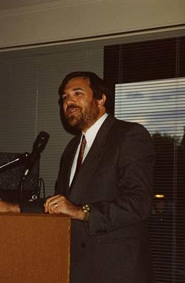 [David Levi speaking at a podium at an unknown event]
