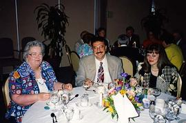 [Two unknown women and an unknown man sitting at a table at an unknown event]