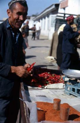 Man selling red peppers at the market