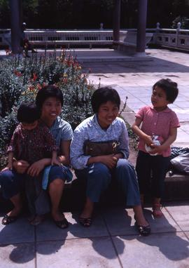 Two women sitting by a garden with two little girls standing next to them