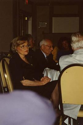 [Dr. Irving and Phyliss Snider sitting at a table with unknown people at an unknown event]