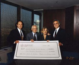 [Dr. Irving and Phyliss Snider posing with two unknown men holding a donation check for Jewish Fa...