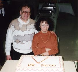 [Bernie Simpson and his wife Lee posing in front of a cake]