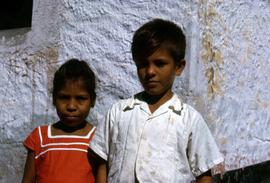 Girl in a red dress and a boy in a white shirt posing in front of a white washed wall