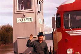 Man standing next to a red bus at a ferry station, part of Dawson City, Yukon