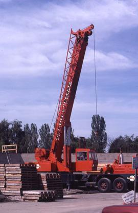 Red crane with wooden pallets to the left of it