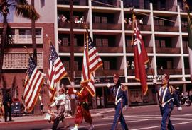 Four Shriners in uniform marching with flags