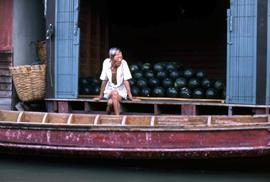 Elderly man sitting on a dock with a red boat in front of him