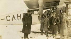 [Five unknown men standing in front of a plane in the snow]
