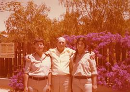 Ben Dayson standing between two women [possibly Israeli soldiers] at David Ben Gurion's cabi...