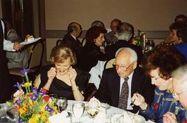 [Dr. Irving and Phyliss Snider sitting at a table eating at an unknown event]