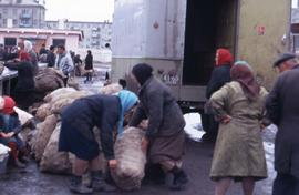 Group of women handling bags of potatoes in front of a truck and surrounded by other people in a ...
