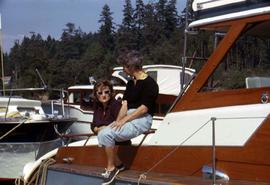 Phyliss Snider and an unknown woman sitting on a boat with other boats in the background