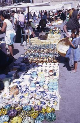 People standing around rows of different bowls for sale lined up on the ground