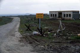 "Landscape scene with a sign reading ""Frontier Ahead"", a road, and a damaged building"