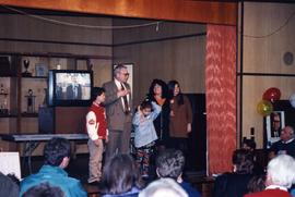 [Bernie Simpson and his family on a stage]