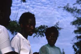 Three unknown children with trees and a blue sky with clouds behind them