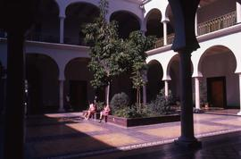 Three unknown people sitting next to trees in the centre courtyard of a building