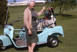 Unknown woman posing for the camera beside a light blue golf cart