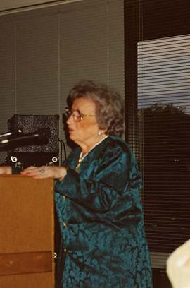 [Esther Dayson speaking at a podium at an unknown event]