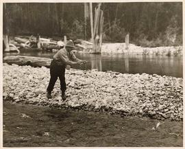 Fly-fisherman on rocky shore