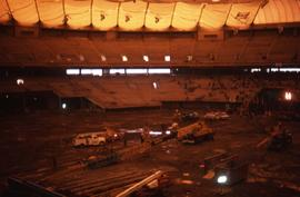 Interior of BC Place with trucks and vans on the soil floor