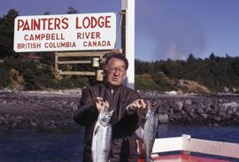 "Unknown man holding two fish and a sign in the background that reads: ""Painter's Lodge,..."