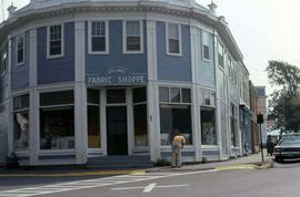 "Blue building with white trim with a sign that reads: ""Vivian's Fabric Shoppe"""