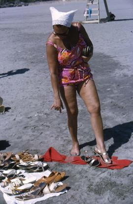 Phyliss Snider, wearing a pink bathing suit, looking at shoes for sale