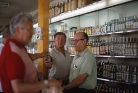 Three unknown men standing in a store