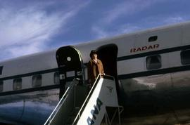 Phyliss standing on the steps leading to a plane