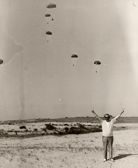 'Israeli Paratroopers,' [Ben Wosk ?] standing in open field, parachutists in the sky above him