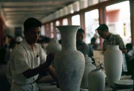 Men painting vases in a factory