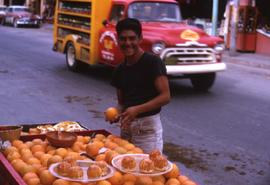 Unknown man holding an orange with a table of oranges in front of him